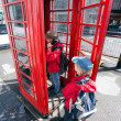 Boy talking in pay phone box - Stock Photo
