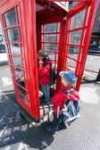 Jongen praten in pay telefoon vak — Stockfoto