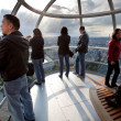 Tourists in the London eye cabin observing city from above - Stock Photo