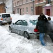 Stock Photo: Pushing stuck car in snowy street after heavy snowfall in Riga