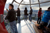 Tourists in the London eye cabin observing city from above — Stock Photo