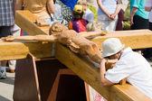 Praying woman at large wooden crucifix — Stock Photo