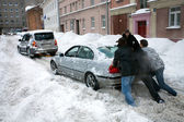Pushing stuck car in snowy street after heavy snowfall in Riga — Stock Photo