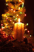 Candle and the christmas tree — Stock Photo