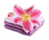 Stacked towels with pink lily — Stock Photo