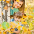 Young family in autumn forest — Stock Photo