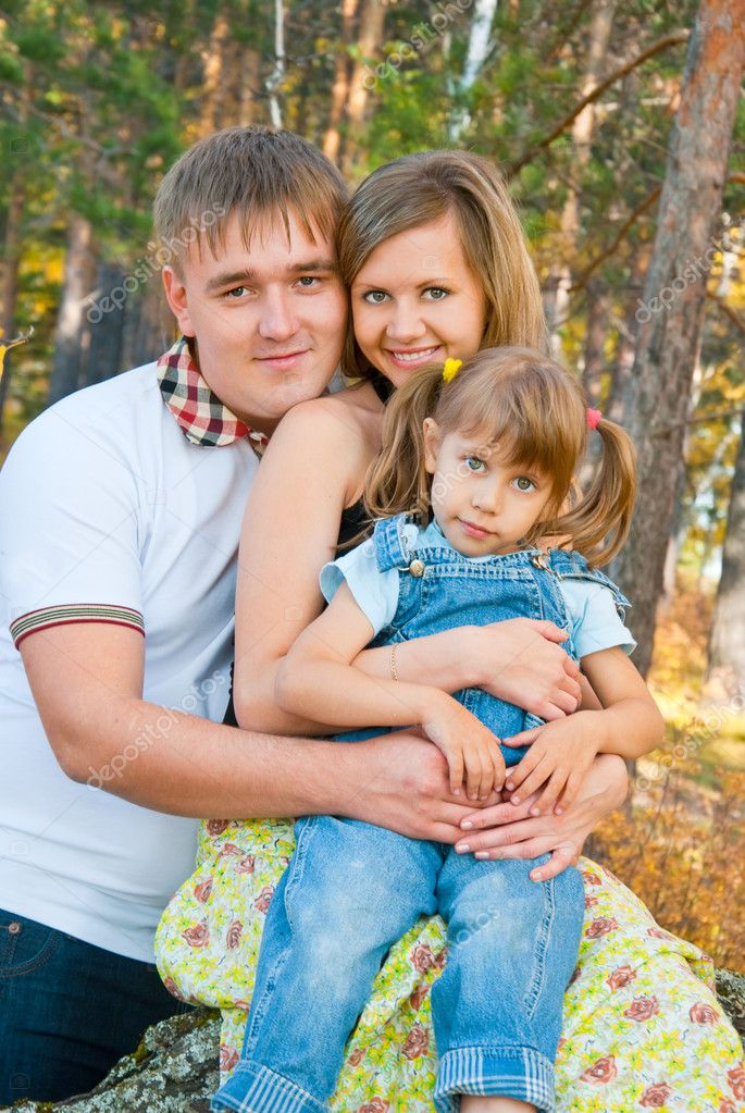 Young family in autumn forest — Stock Photo #7280952