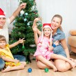 Family under the Christmas spruce — Stock Photo #7415200