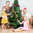 Family under the Christmas spruce — Stock Photo