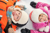 Boy and girl lying on the snow — Stock Photo