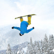 Snowboarder at jump inhigh mountains at sunny day - Stock Photo