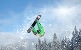 Snowboarder at jump inhigh mountains at sunny day — Stock Photo