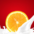 Splashing milk with orange — Stock Photo
