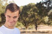 Jongeman met bomen op achtergrond — Stockfoto