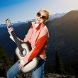 Young woman standing with guitar, against mountain landscape — Stock Photo #7168667