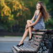 Magnificent brunette sits on bench which is on city street — Stock Photo #7168668