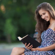 Beautiful brunette woman sits on bench and read book on city str — Stock Photo #7168675
