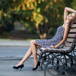 Magnificent brunette sits on bench which is on city street — Stock Photo #7168676