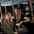 Three happy young women in a nightclub sitting at the bar — Stock Photo
