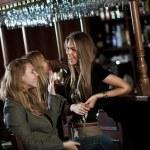 Три счастливые молодые женщины в ночном клубе, сидя в баре — Стоковое фото