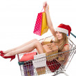 Christmas woman in santa hat sitting in shopping cart over white — Stock Photo