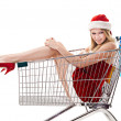 Christmas woman in santa hat sitting in shopping cart over white — Stock Photo #7927864