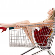 Christmas woman in santa hat sitting in shopping cart over white — Stock Photo #7927873