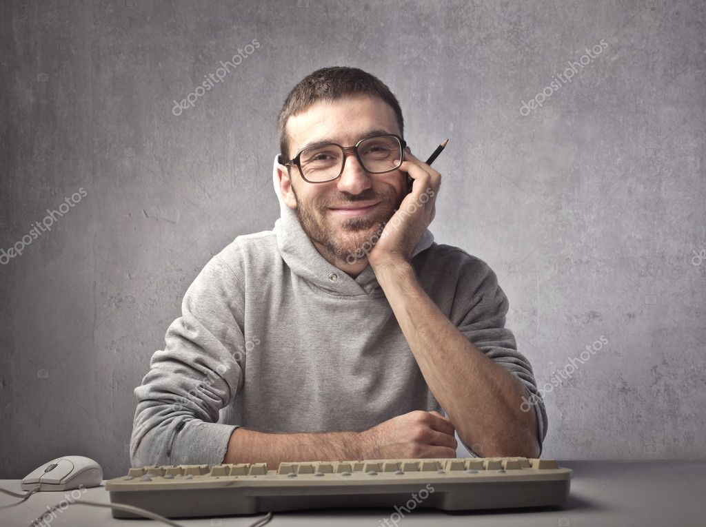 Smiling man sitting in front of a computer keyboard — Stock Photo #7260657