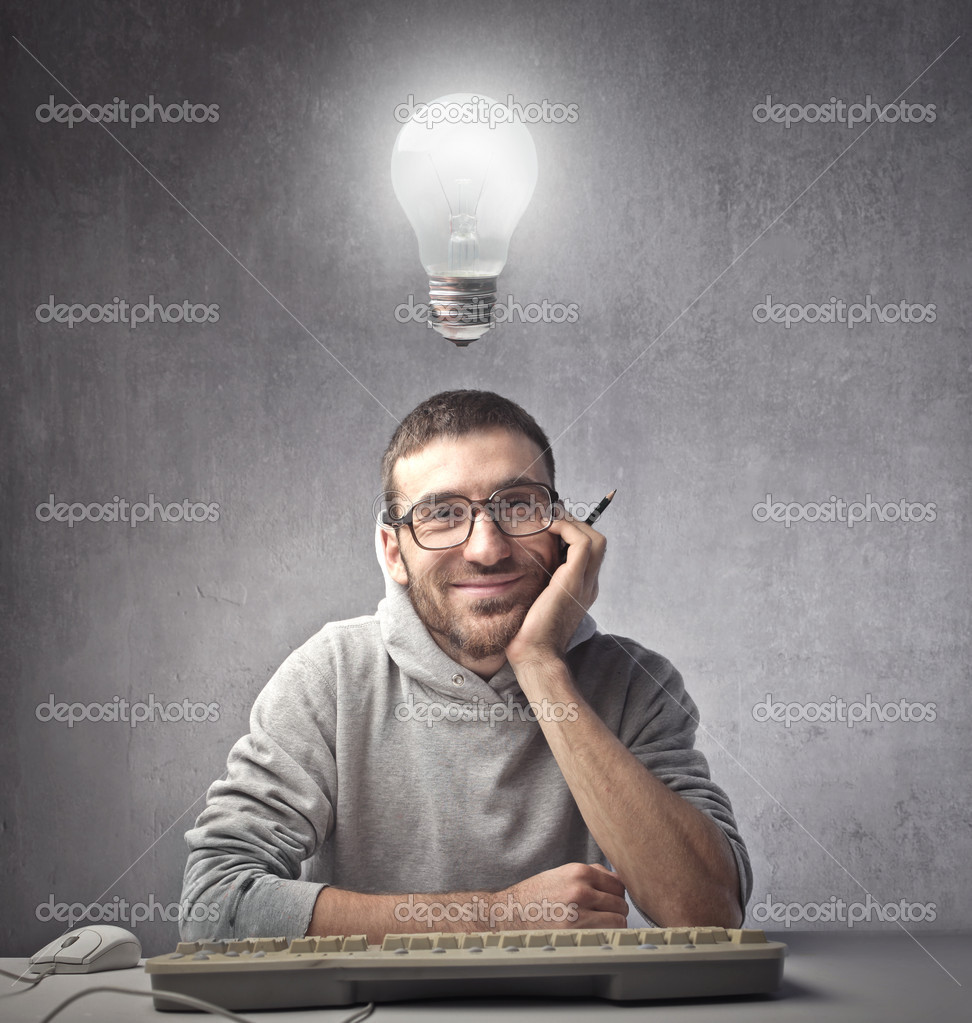 Smiling man sitting in front of a computer keyboard with light bulb over his head  Stock Photo #7260695