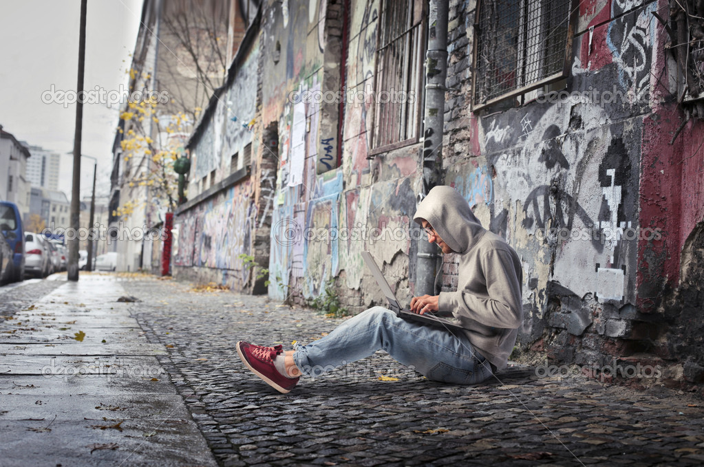 Young man sitting on a city street and using a laptop  Stock Photo #7262734
