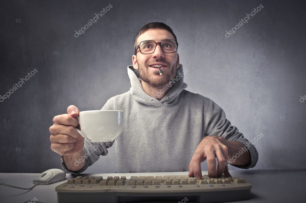 Young nerd typing on a keyboard while holding a cup of coffee — Lizenzfreies Foto #7264033