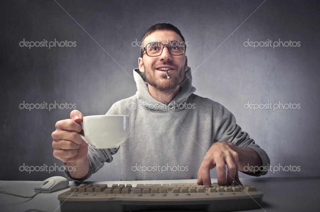 Young nerd typing on a keyboard while holding a cup of coffee — Stok fotoğraf #7264033