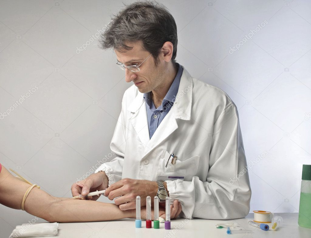 Doctor injecting a vaccine in a man's arm  Stock Photo #7279739