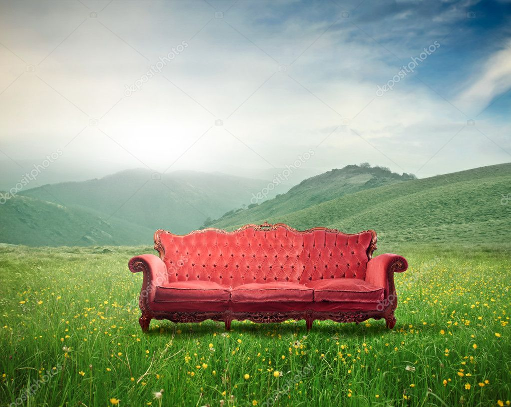 Red velvet sofa on a green meadow — Stock Photo #7321515