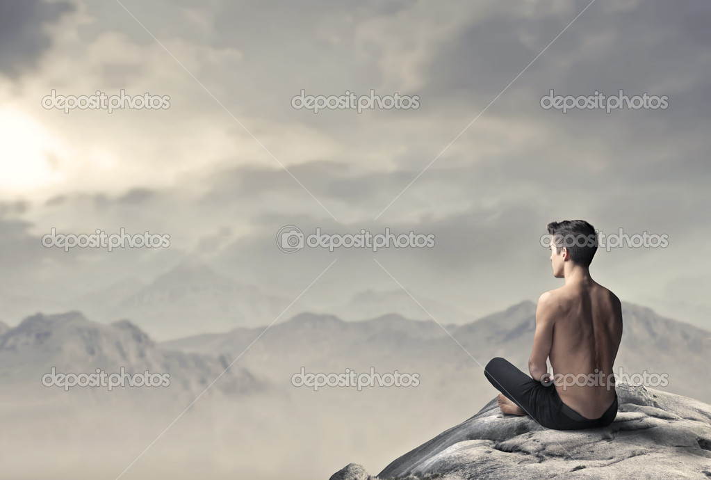 Handsome bare-chested man sitting on a peak over the mountains — Stock Photo #7322441