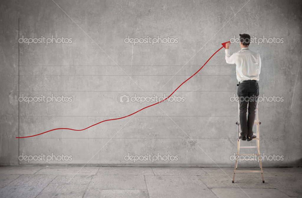 Young businessman on a ladder drawing a positive trend chart — Stock Photo #7626840