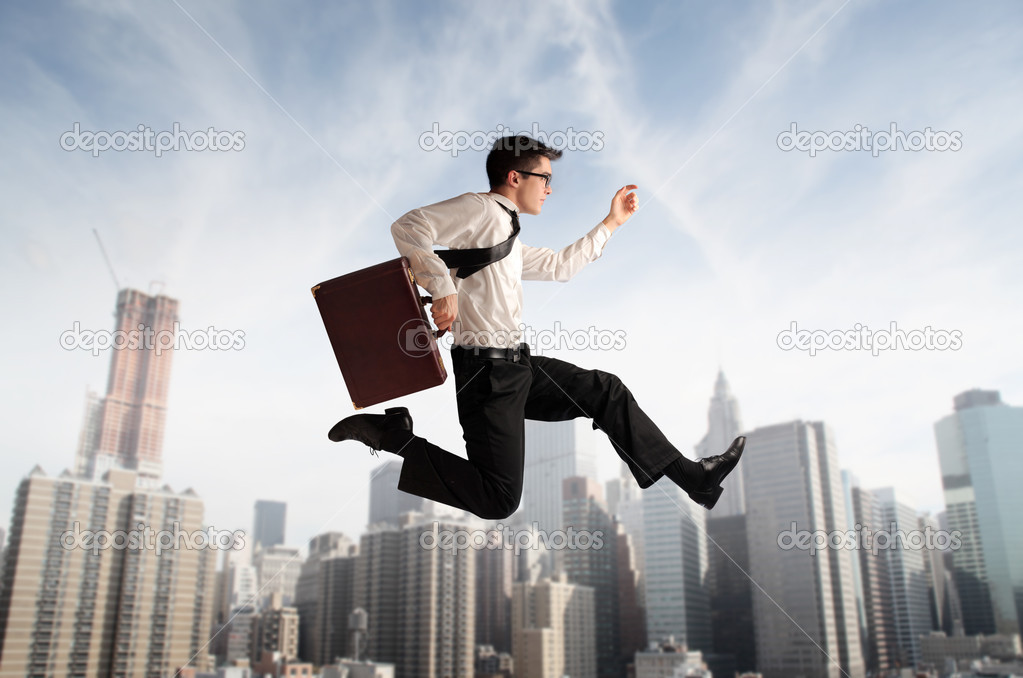 Young businessman running fast over a big city — Stock Photo #7627097