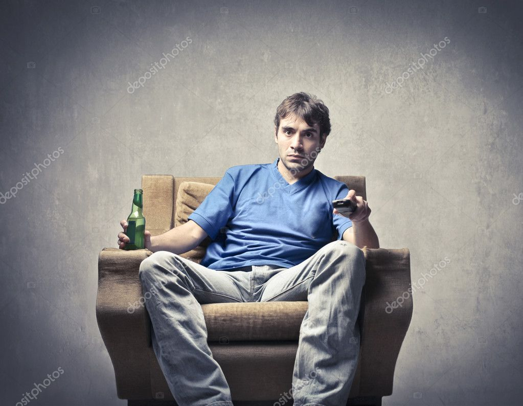 Young man sitting on an armchair and holding a remote control and a beer — Stok fotoğraf #7627923
