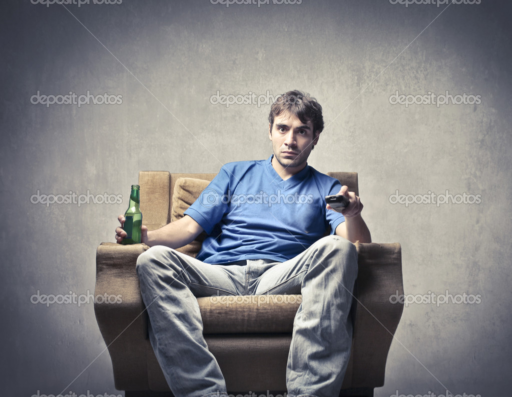 Young man sitting on an armchair and holding a remote control and a beer  Stock Photo #7627923
