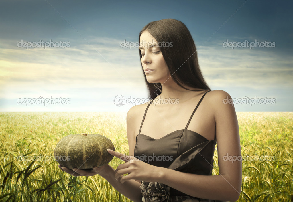 Beautiful woman holding a pumpkin on a wheat field — Stock Photo #7628963