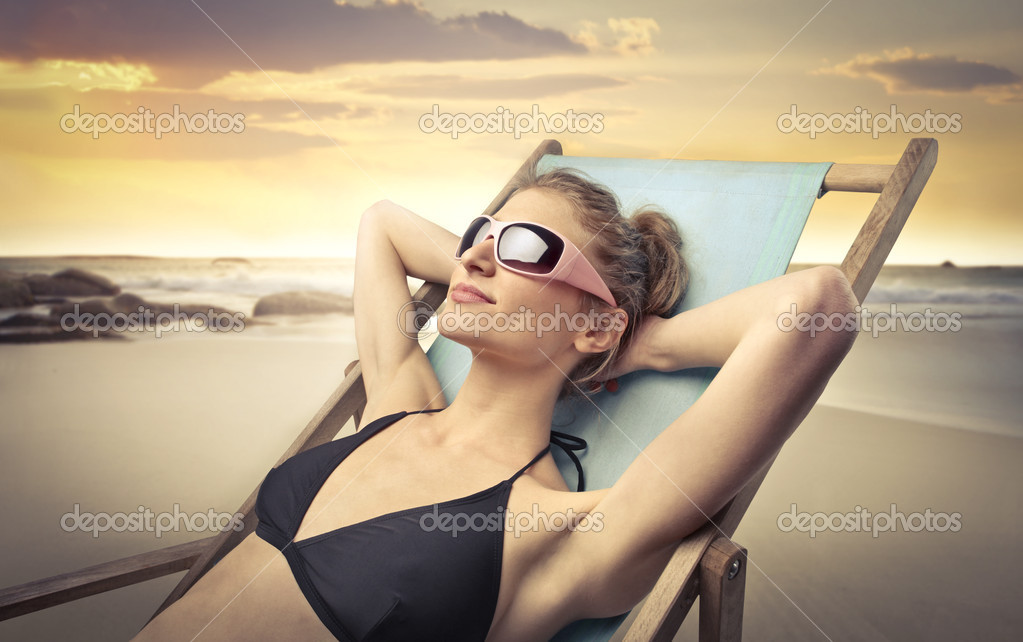 Smiling beautiful woman lying on a deckchair and tanning at the seaside — Stock Photo #7629083