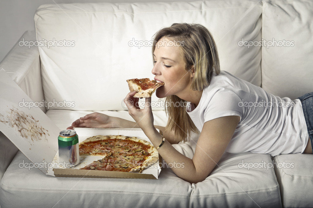 Young woman lying on a sofa and eating pizza — Stock Photo #7682786