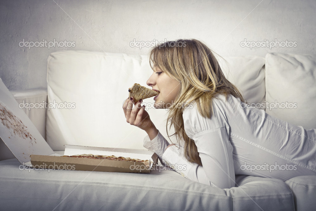 Young woman lying on a sofa and eating pizza — Stock Photo #7682798