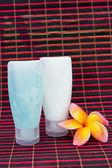 Shampoo bottles and frangipani flower — Stock Photo