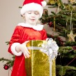 Little girl as Santa Claus with Christmas present — Stock Photo #7587559