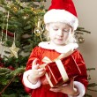 Little girl as Santa Claus with Christmas present — Stock Photo #7843034