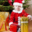 Little girl as Santa Claus with Christmas presents — Stock Photo #7843061