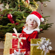 Little girl as Santa Claus with Christmas presents — Stock Photo #7843071