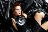 Portrait of sitting woman wearing latex clothes — Stock Photo