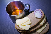 Steel cup, bread, cheese and onion — Stock Photo